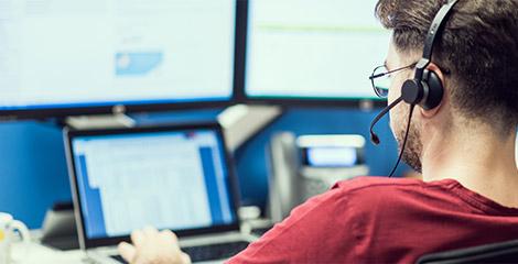 Un bărbat stă la biroul său, poartă căști și tastează pe laptopul ce afișează foi de calcul.