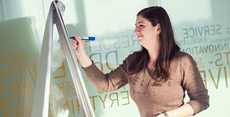"""O femeie scrie pe o tablă mare albă într-o cameră de ședințe ADP. În spatele acesteia se află un geam opac. Cuvintele: """"Serviciu"""", """"Excelență"""" și """"Rezultate"""" sunt întipărite în sticlă."""