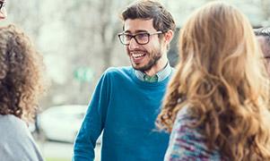 Un bărbat și două femei stau afară, pe o stradă din oraș discutând despre ziua lor.