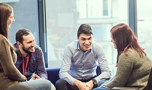 Un grup format din doi bărbați și două femei stau în fața unor geamuri mari într-un birou, implicați într-o discuție despre munca lor la ADP.