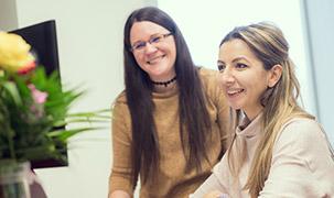 Două femei, una stând jos și cealaltă în picioare, privesc la ecranul unui computer. Acestea zâmbesc și sunt fericite că sunt la serviciu. Pe birou se află și o vază cu flori.