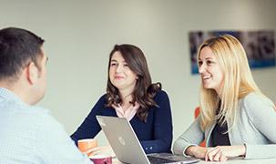 Două femei stau la o masă în fața unui bărbat. O femeie are laptopul deschis în timp ce colegii acesteia împărtășesc idei.