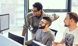 Trei bărbați colaborează în fața unei console pe care se află mai multe ecrane de computer. Doi dintre aceștia stau jos, în timp ce al treilea stă în picioare și se apleacă puțin pentru a vedea mai bine ce apare pe ecran în partea dreaptă.