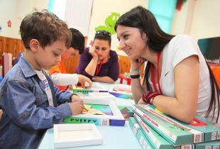Două femei voluntare stau la o masă cu doi băieței și îi ajută la citit și alte activități educaționale.