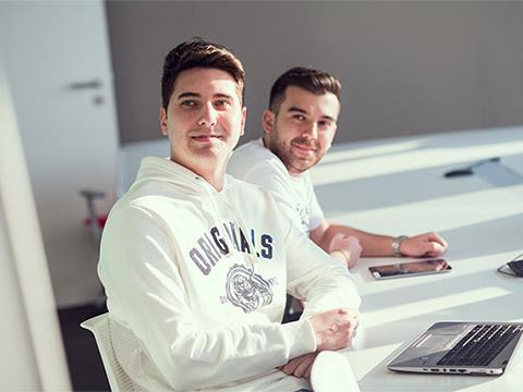 Doi bărbați zâmbesc spre cameră și stau unul lângă celălalt la o masă într-un spațiu de lucru la ADP.