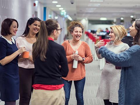 Un grup de șase femei stau lângă un rând de compartimente, gesticulând și râzând. O femeie ține în mână o hârtie rulată, în timp ce o altă femeie ține în mână o cană de cafea.