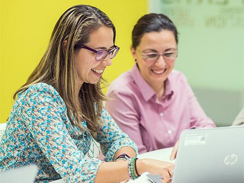 Două femei stau în fața unui laptop deschis, vorbesc și zâmbesc, în timp ce una dintre cele ele arată ceva pe ecran.