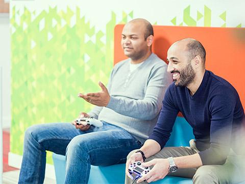 Doi bărbați stau pe o bancă viu colorată. Aceștia sunt implicați într-o discuție activă și prietenoasă cu cineva care nu apare în fotografie.