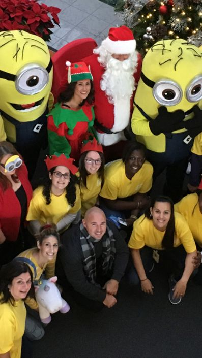 holiday picture of Santa, an elf, minions and associates in yellow t-shirts