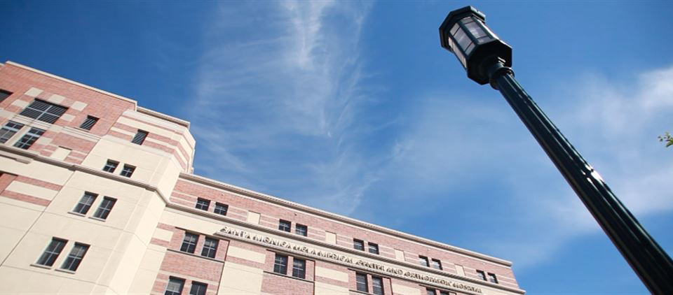 Skyward view of UCLA Health building and lamppost against blue sky and wispy clouds
