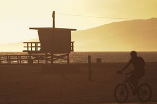Beach sunset scene with lifeguard tower and bicyclist in the foreground