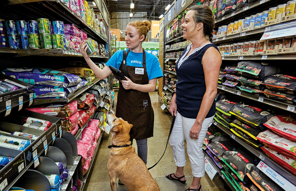 In a store aisle, a young female Petco Guest Advisor helps a customer select the right dog food, while her seated dog, looks up at the food choice eagerly.