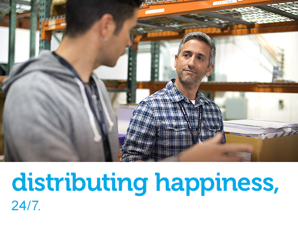 "Two men with clipboards are discussing orders and merchandise in a distribution center setting. Text across the image reads, ""distributing happiness, 24/7."""