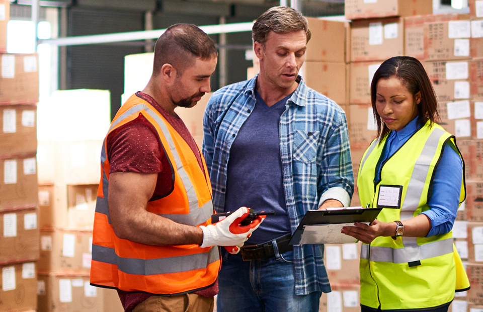 A diverse group of three distribution center workers consult a clipboard and discuss inventory with stacks of labeled boxes in the background.
