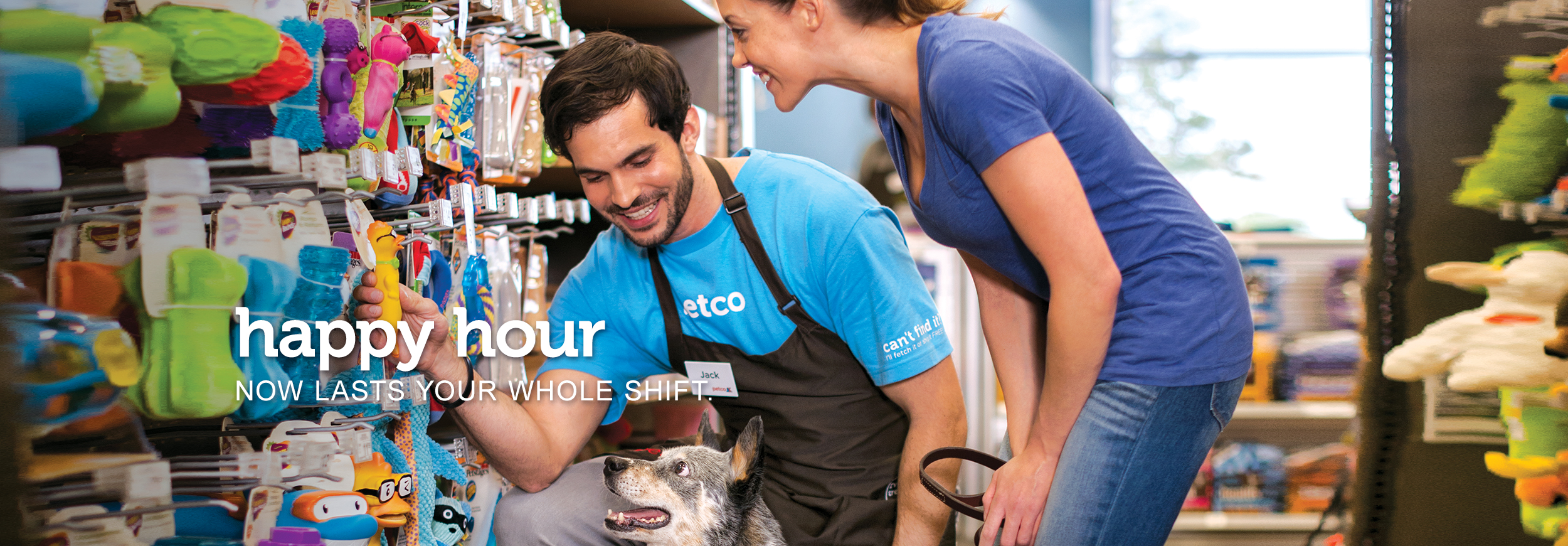 "Male store employee showing a dog and his owner a new toy on the wall. The dog's expression is very excited. Text across the image reads, ""happy hour now lasts your whole shift."""