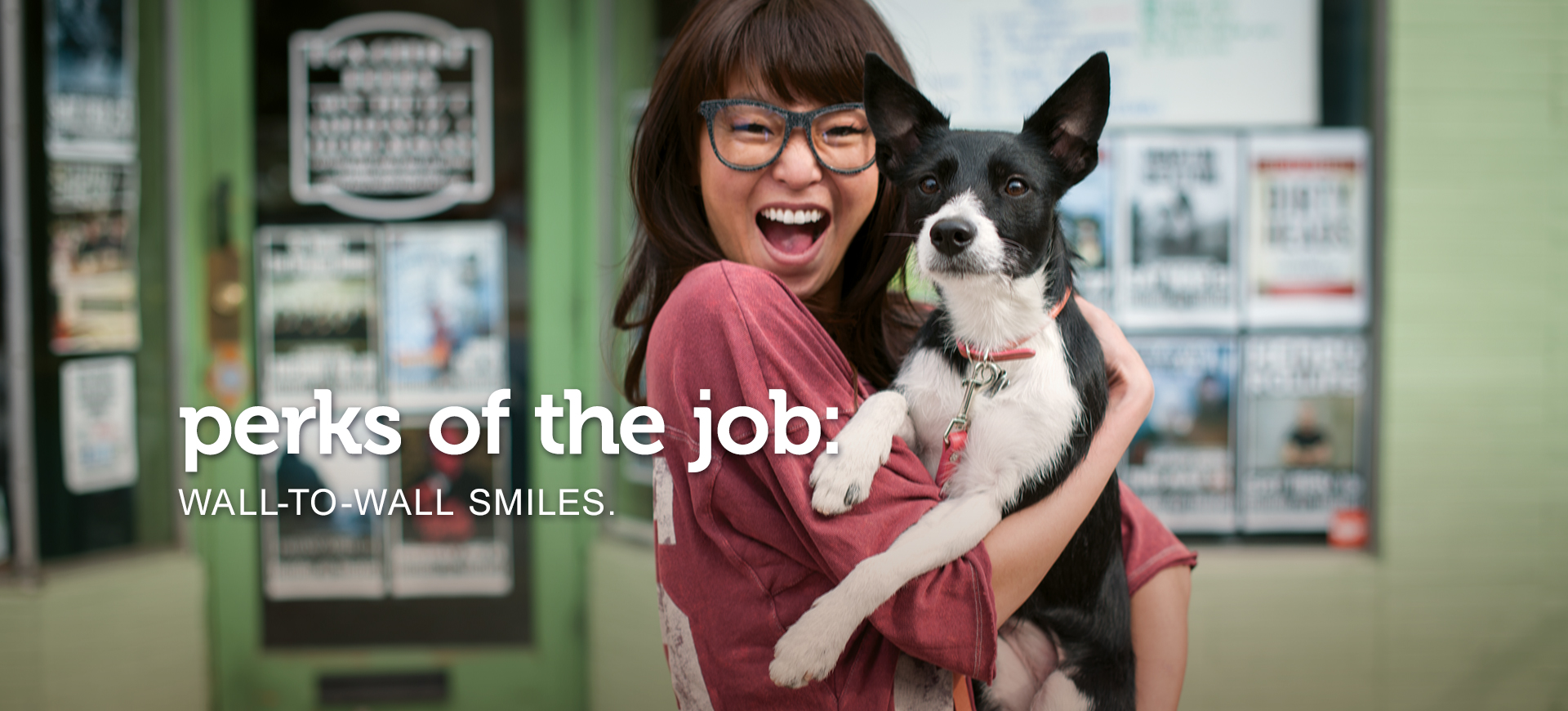 "Excited young woman in glasses holds her equally happy-looking black and white dog as they look at the camera. Text across the image reads, ""perks of the job: wall-to-wall smiles."""