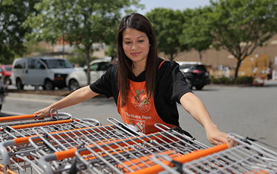 Female Home Depot associate gathering shopping carts in the parking lot.