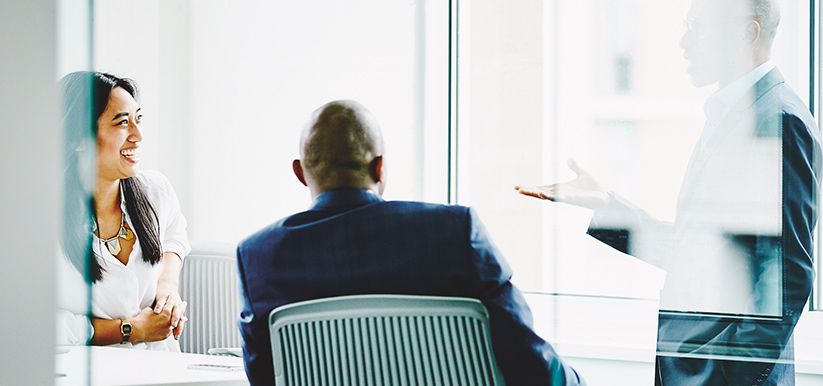 Two men and a woman having a discussion in a conference room