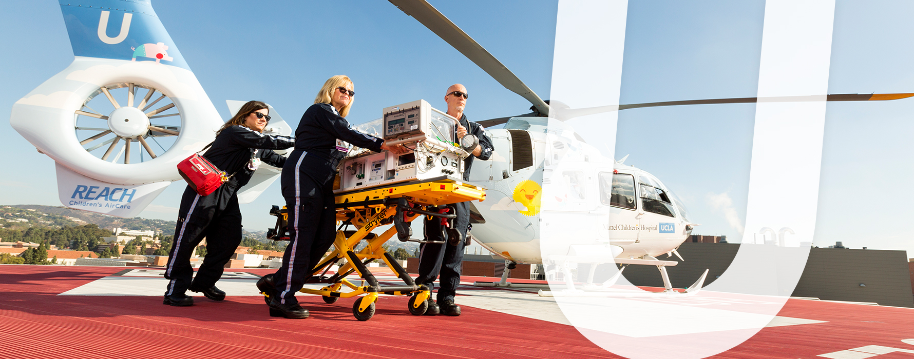 Three nurses standing in front of a helicopter on a helipad transporting patient