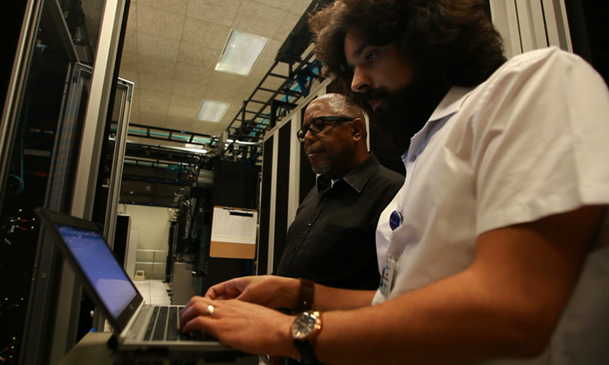 Information technologists working in a server room.