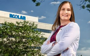 woman standing with folded hands in front of ecolab