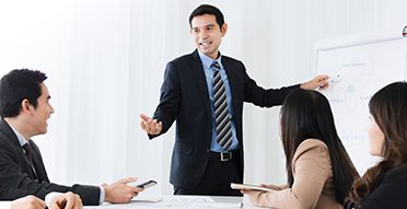 Man points to presentation board in a meeting with colleagues