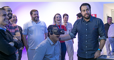 Employee wears virtual reality headset while others watch his reactions