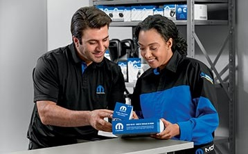 Two employees look at Mopar® aftermarket parts