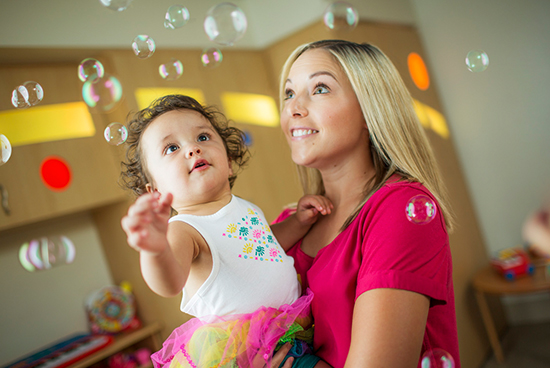 Mother with the child looking at bubbles and smiling