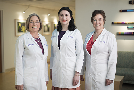 Three female doctors are smiling at camera