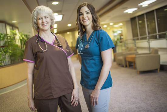 Two female nurse and doctors are posing to camera with smile