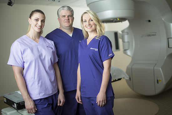 nurse and doctors in front of MRI machine