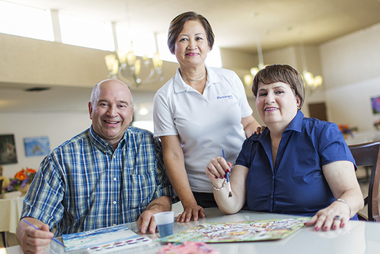 Nurse with a old couple who painting on papers