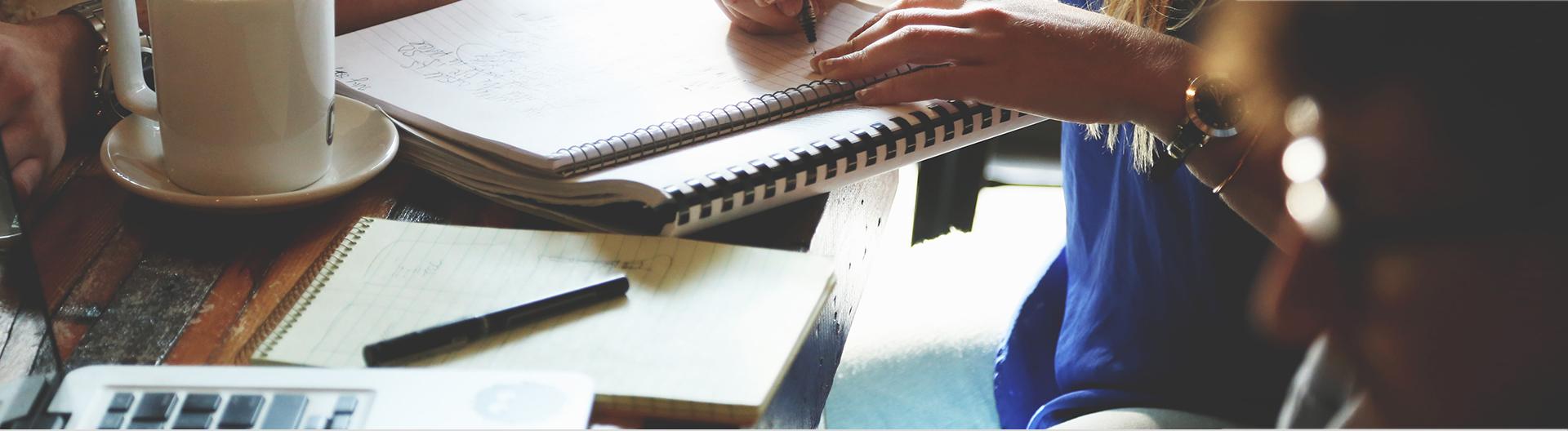 Girl writing notes on her study table with coffee mug