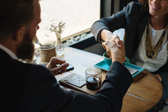 Male and female partners discussing in coffee shop with coffee