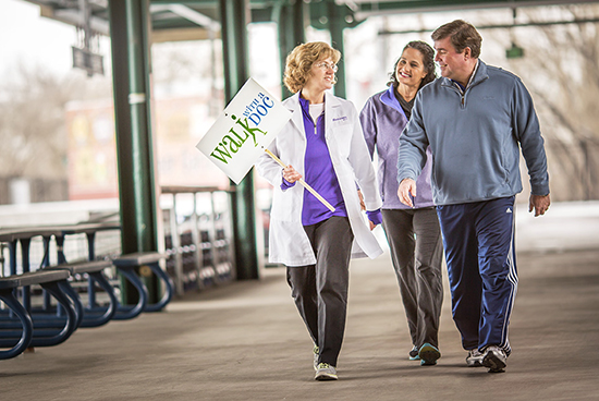 "doctor holding sign boad of ""walk along with doctor"" and walking along with the patient"
