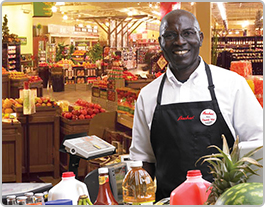 A smiling male employee looks up from scanning a customer's groceries at the check-out.