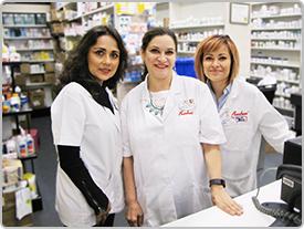 Three female pharmacists stand smiling together behind a pharmacy counter.