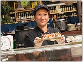 Female sushi chef, Tuyet, smiles from behind a counter as she lifts a plate of sushi.