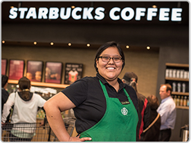 Female Starbucks manager, Sasha, stands smiling with her hands on her hips in front of the in-store Starbucks Coffee shop she manages.