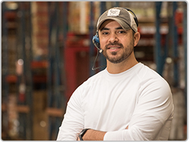 A male employee with a headset on stands smiling with his arms crossed.