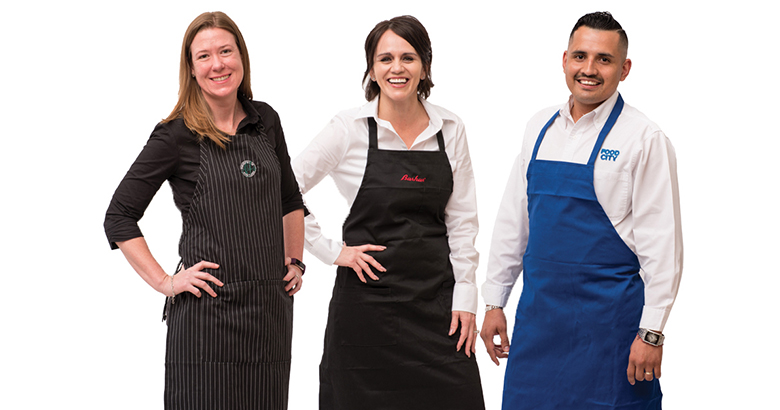 Two female employees and one male employee, each wearing an apron, stand smiling together.
