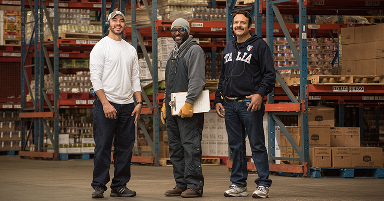 Three male employees, dressed in casual street clothes, stand in the middle of a warehouse together.
