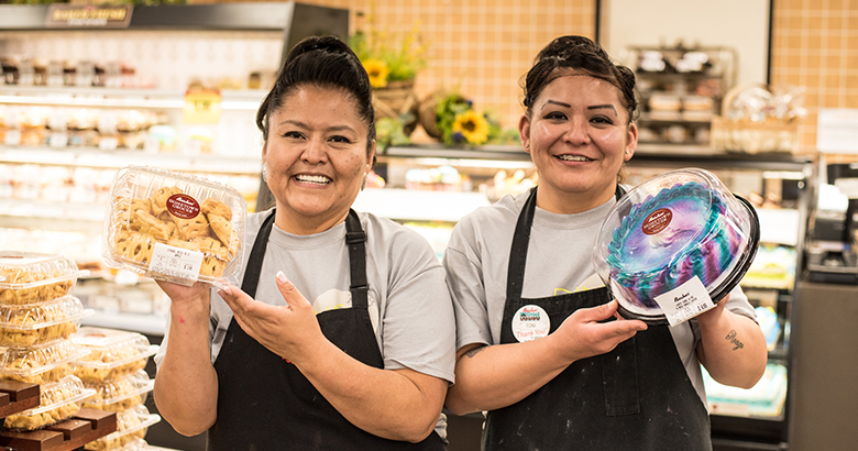 Two female employees wearing aprons stand smiling in the middle of the bakery area, each holding up a dessert.