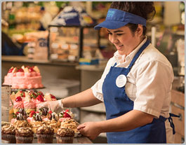 A female employee smiles as she puts the finishing touches on some cupcakes before placing them in the bakery display case.