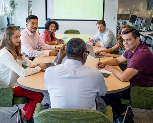 Picture of 7 Vanguard crew at a meeting in an open spaced conference room