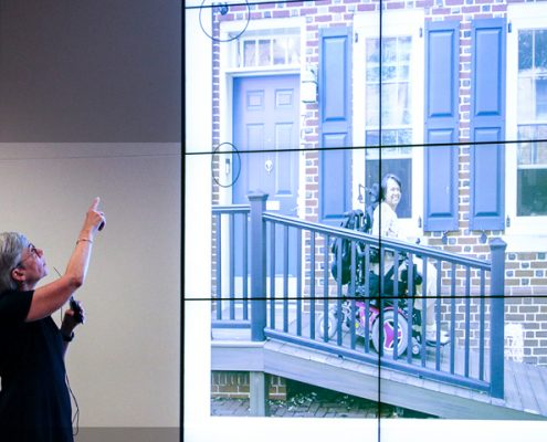 Picture of Susan Tachau at the event, showing a photo of a woman in a wheelchair who is outside her home that was equipped with accessibility features.