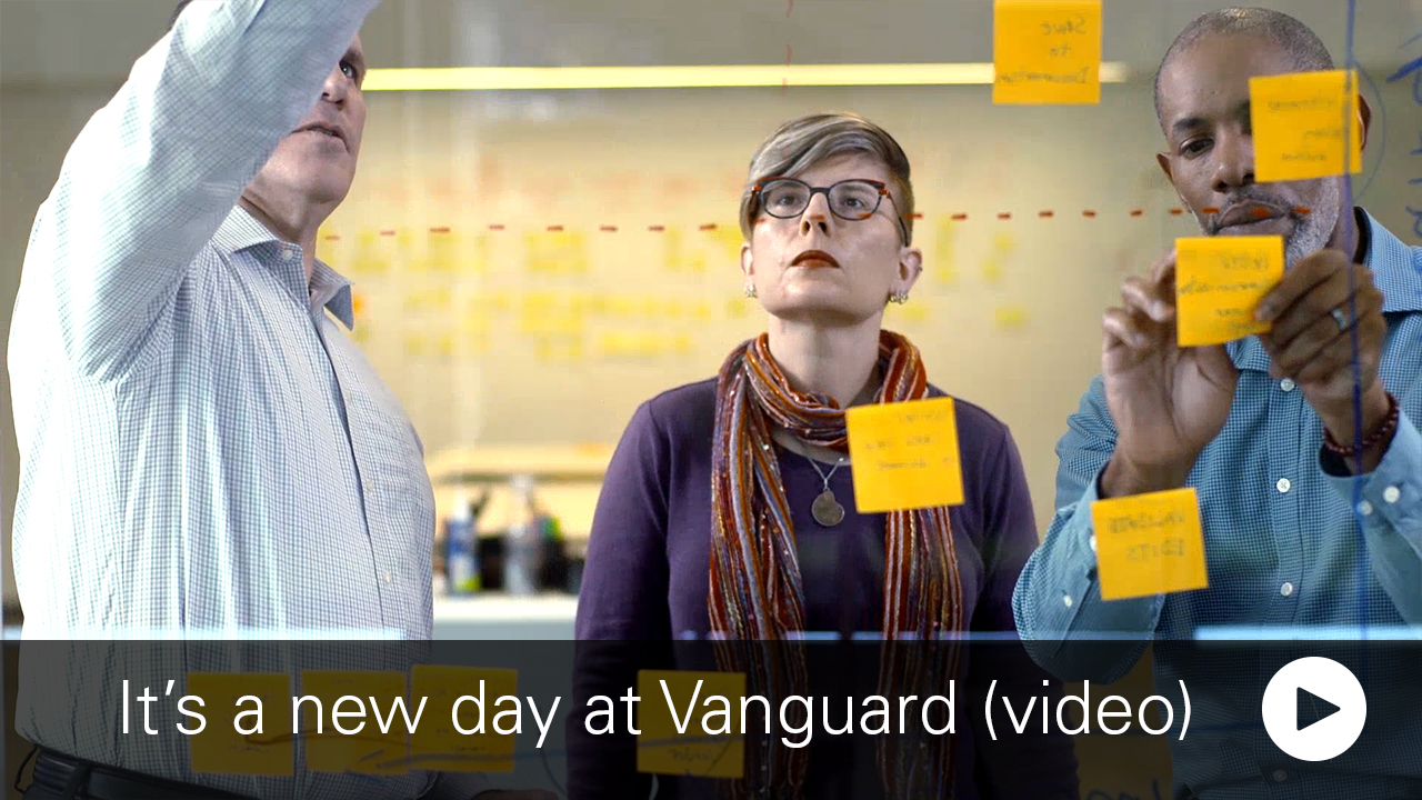 3 Vanguard employee collborating at a whiteboard
