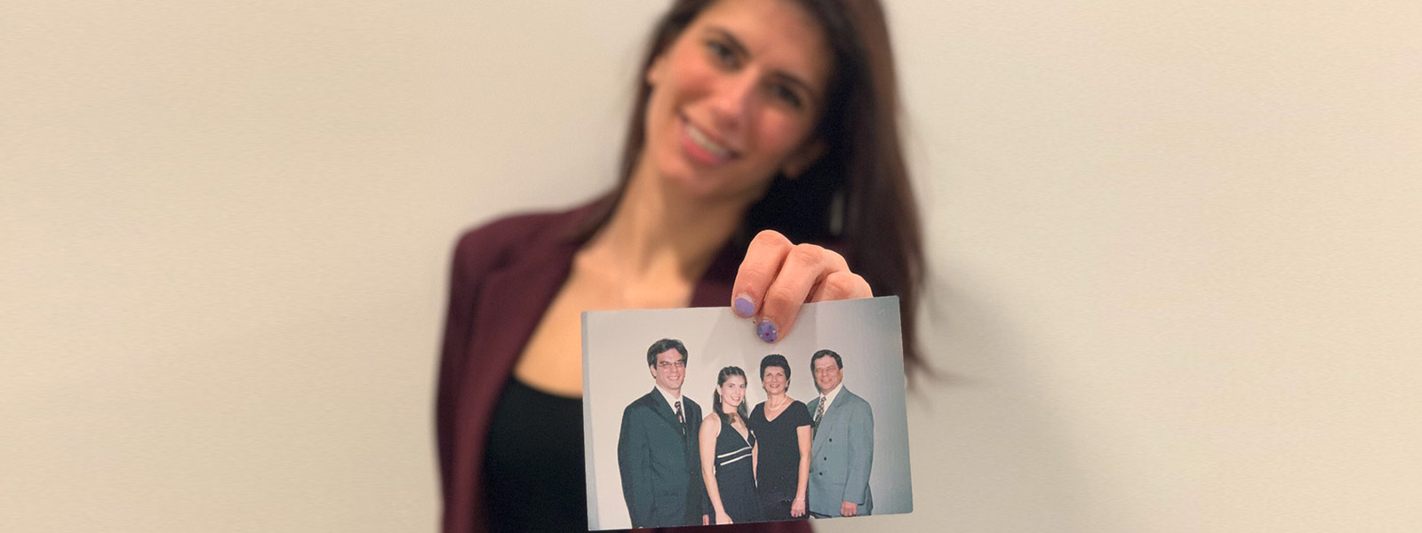 Crew member Kristin holding a picture of her family, parents and brother
