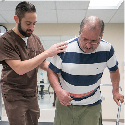 Male physical therapist assisting male patient at JPS rehabilitation facility